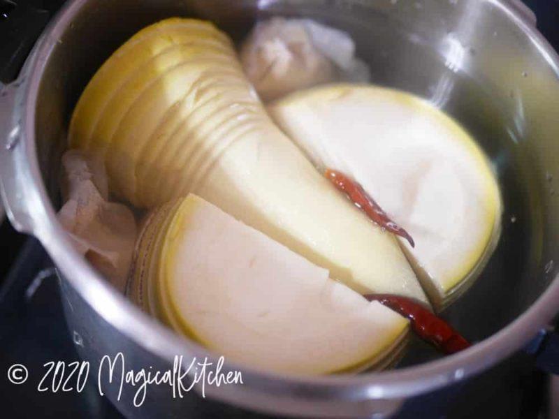 圧力鍋にたけのこ、ぬか、赤唐辛子を入れる